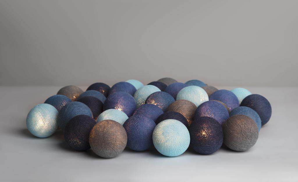 En blå ljusslinga från Irislights. Handgjorda bollar av bomull. Dekorationsbelysning för vardagsrum och sovrum.