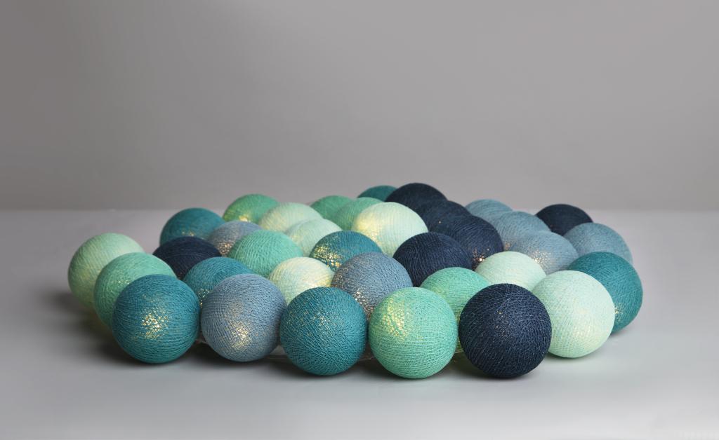 En blå ljusslinga med bollar som är handgjorda av bomull.