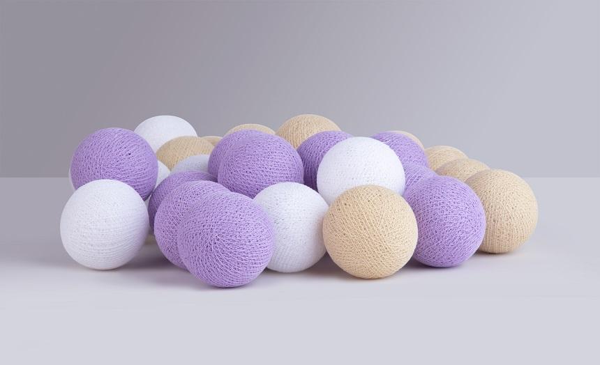 """Ljusslinga """"Lilac"""" är en nyhet inför vår-, och sommarsäsongen 2021. Kombinationen av vita och beiga bomullsbollar ger ljusslingan en mjuk och varm känsla, samtidigt som de lavenderlila bollarna tillsätter en uns av lekfullhet."""